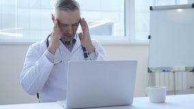Dor de cabeça, doutor cansado que trabalha no portátil foto de stock