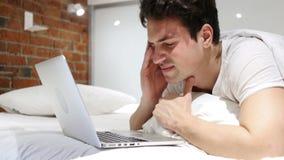 Dor de cabeça, homem cansado que trabalha no portátil na cama video estoque