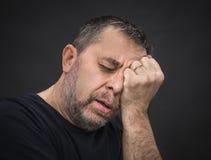 Dor de cabeça. Homem com a cara fechado à mão Foto de Stock Royalty Free