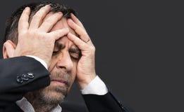 Dor de cabeça Homem com a cara fechado pelas mãos Fotografia de Stock