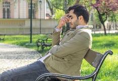 Dor de cabeça, homem estratificado que senta-se em um parque no banco foto de stock