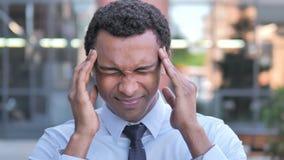 Dor de cabeça, homem de negócios africano forçado incômodo video estoque