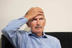 Dor de cabeça idosa do homem O homem espreme sua cabeça foto de stock royalty free
