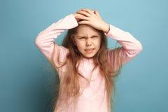 A dor de cabeça Menina adolescente em um fundo azul Expressões faciais e conceito das emoções dos povos foto de stock