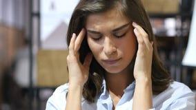 Dor de cabeça, moça frustrante que senta-se no escritório do sótão imagens de stock royalty free