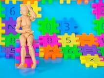 A dor de cabeça modelo plástica do boneco de ação e o assento no cubo completo da cor fazem do número plástico no fundo azul Conc Fotos de Stock