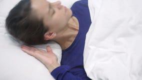 Dor de cabeça, mulher latino-americano incômoda com a dor que acorda do sono, noite filme