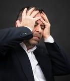 Dor de cabeça. Homem com a cara fechado pelas mãos Imagem de Stock
