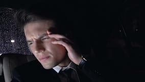Dor de cabeça sobrecarregado do sofrimento do homem de negócios Tired que senta-se no banco traseiro do carro, noite filme