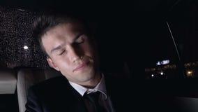 Dor de cabeça sobrecarregado do sofrimento do homem que senta-se no banco traseiro do carro, esforço de trabalho video estoque