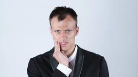 Dor de dente Homem novo frustrante que toca em seu mordente, fundo branco filme