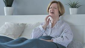 Dor de dente, mulher superior idosa com a dor de dente que senta-se na cama filme