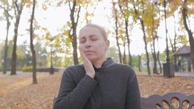 Dor de dente, uma mulher que sofre da dor nos dentes, sentando-se em um parque em um banco filme