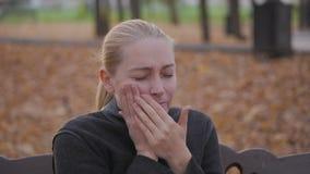 Dor de dente, uma mulher que sofre da dor nos dentes, sentando-se em um parque em um banco video estoque