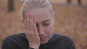 Dor de dente, uma mulher que sofre da dor nos dentes, sentando-se em um parque em um banco vídeos de arquivo