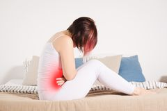 Dor de estômago, mulher com a dor abdominal que sofre em casa imagem de stock
