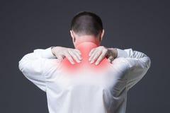 Dor de pescoço, homem com dor lombar no fundo cinzento fotos de stock