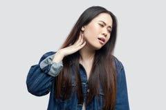 Dor de pescoço Retrato da jovem mulher asiática moreno bonita doente no incômodo estando do sentimento do revestimento azul ocasi fotos de stock