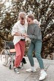 Dor deficiente do sentimento do homem ao tentar levantar-se da cadeira de rodas foto de stock royalty free
