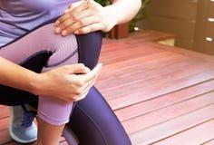 Dor do joelho Lesão de joelho de sofrimento da jovem mulher ao exercitar e ao correr Conceito dos cuidados médicos e do esporte fotos de stock