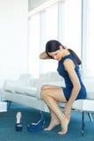dor do pé A jovem mulher faz massagens seus pés cansados imagens de stock royalty free