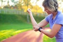 Dor do sentimento da jovem mulher em seu cotovelo durante o exercício do esporte no st imagens de stock