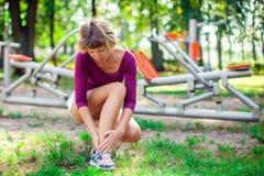 Dor do sentimento da jovem mulher em seu pé durante o exercício do esporte no foto de stock royalty free