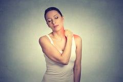 dor Mulher com o ombro doloroso do pescoço colorido no vermelho foto de stock royalty free