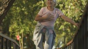Dor no peito de sentimento da mulher adulta durante a manhã que movimenta-se no parque, cuidados médicos, curso vídeos de arquivo
