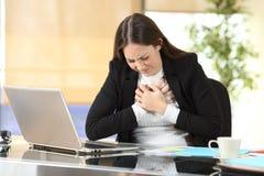 Dor nova da caixa do sofrimento da mulher de negócios no escritório imagens de stock royalty free