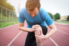 Dor running do sentimento do atleta devido ao joelho ferido Fotografia de Stock