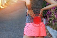 Dor traseira Mulher atlética da aptidão que fricciona os músculos de sua mais baixa parte traseira Ferimento do esporte Imagens de Stock