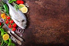 Dorada, свежая рыба с овощем, лимоном, травами, луком, паприкой, томатами вишни, луком, предпосылкой salton темной винтажной Скоп Стоковые Фотографии RF