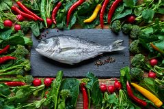 Dorada fish and green vegetables around on old wooden table. Top. Dorada fish and green vegetables around on old wooden table. Dorada, broccoli, chilli pepper Stock Photos