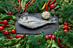 Dorada fish and green vegetables around on old wooden table. Top. Dorada fish and green vegetables around on old wooden table. Dorada, broccoli, chilli pepper Stock Photography