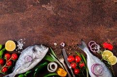 Dorada, frischer Fisch mit Gemüse, Zitrone, Kräuter, Zwiebel, Paprika, Kirschtomaten, Zwiebel, Salz Stockbilder