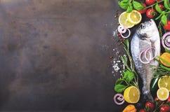 Dorada, pescado fresco con la verdura, limón, hierbas, cebolla, paprika, tomates de cereza, cebolla, fondo oscuro del vintage del Fotografía de archivo