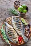 Dorade grelhado Royale Fish na placa de madeira fotografia de stock royalty free