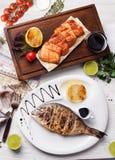 Dorado,三文鱼在上面,静物画,木板条桌烤了 免版税库存照片