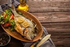 Dorado arrostito con il limone, il timo, i rosmarini e l'insalata fresca su Th fotografia stock