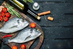 Dorado cru de poisson de mer avec des herbes, des épices et une bouteille de vin blanc photographie stock