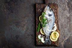 Dorado de los pescados frescos con los ingredientes para cocinar en el tablero de madera La brema de mar o los pescados crudos de fotografía de archivo libre de regalías