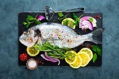 Dorado de poisson frais Poissons et ingrédient crus de dorado pour faire cuire à bord Dorade ou poissons de dorada sur la table d Photos libres de droits