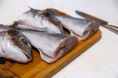 Dorado fish on a cutting board knife cut half. Dorado fish on a cutting board knife cut in half Royalty Free Stock Photo