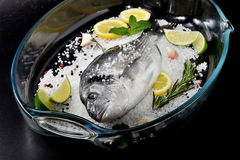 Dorado fish is in glass dish with salt, rosemary, garlic, lime a Royalty Free Stock Photography