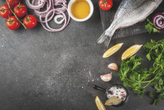 Dorado fish with ingredients for cooking. Fresh raw organic fish Dorado, sea bream with ingredients for cooking lemon, tomatoes, onion, salt, pepper, bay leaf Royalty Free Stock Images