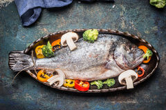 Dorado Fish preparation with vegetables in Casserole in form of fish on rustic background Stock Photo