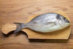 Dorado fish on a wooden board. Top vew Stock Photo
