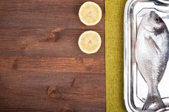 Dorado fish. On a wooden surface with slices of lemon Royalty Free Stock Photography