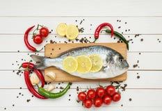 Dorado fisk på träskärbräda med körsbärsröda tomater Royaltyfri Fotografi